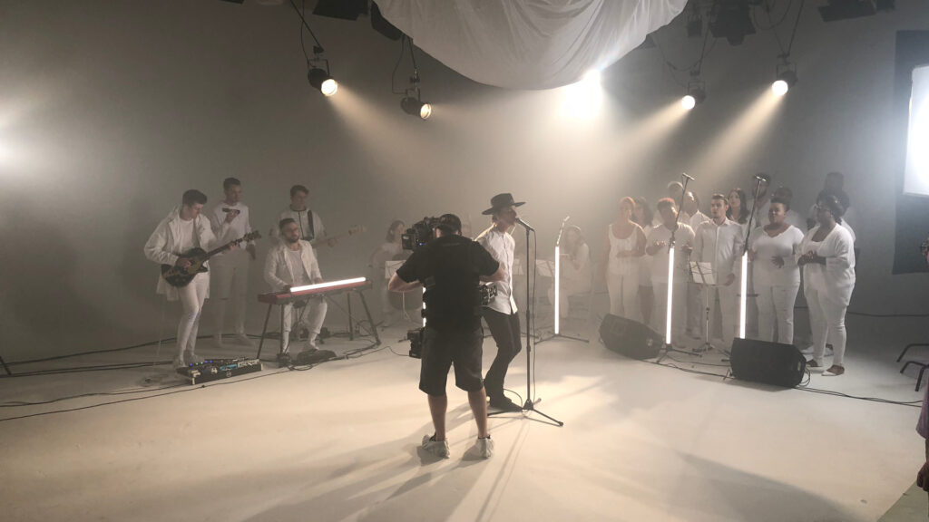 A dramatically-lit music video shoot in a clean, white studio space