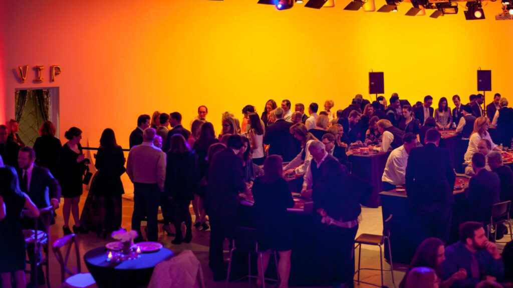 Wide overhead view of a crowd of people playing games during a casino night event in a large studio space