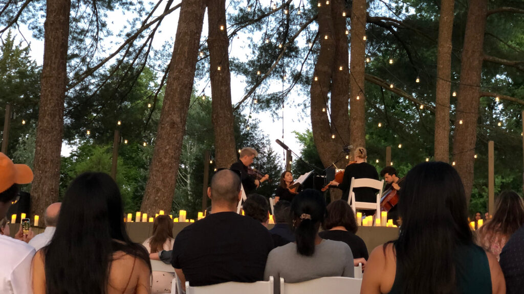 Quartet performing on an outdoor stage in the woods lit by candles and decorative lights